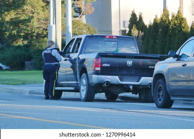 CHILLIWACK, BC/Canada - December 30, 2018: A female officer with the Royal Canadian Mounted Police (RCMP) deals with a driving infraction in Chilliwack, BC, Canada on December 30, 2018.