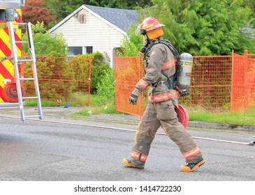 CHILLIWACK, BC/Canada - June 3, 2019: A fire fighter quickly responds to an early morning fire at 46364 Maple ave. in Chilliwack, Canada on June 3, 2019. The vacant home was scheduled for demolition.