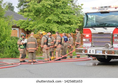 CHILLIWACK, BC/Canada - June 3, 2019: Fire crew with the Chilliwack, BC fire department discuss events after successfully putting out a house fire known to have been deliberately set on June 3, 2019.