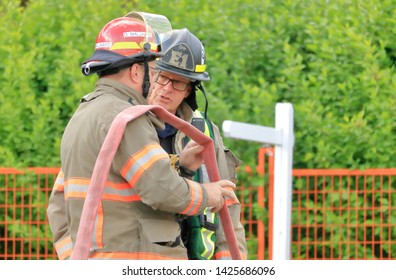 CHILLIWACK, BC/Canada - June 3, 2019: The captain with the Chilliwack, BC fire department discusses events with a fellow fire fighter after successfully putting out a house fire on June 3, 2019.