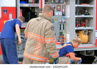 CHILLIWACK, BC/Canada - June 3, 2019: Male and female fire fighters work together after successfully putting out a house fire in Chilliwack, BC, Canada on June 3, 2019.
