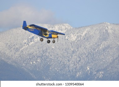 CHILLIWACK, BC/Canada - March 14, 2019: A small Zenair STOL CH 701 descends toward the Chilliwack, BC, Canada airport with the Northshore mountains in the background on March 14, 2019.
