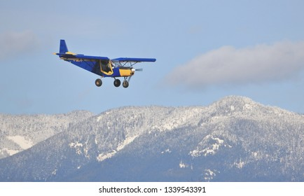 CHILLIWACK, BC/Canada - March 14, 2019: A small Zenair airplane descends toward the Chilliwack, BC, Canada airport with beautiful mountains in the background on March 14, 2019.