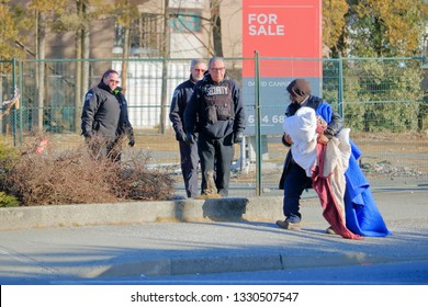 CHILLIWACK, BC/Canada - March 5, 2019: Security personnel evict a homeless man squatting on vacant land at the corner of Williams and Yale Road in Chilliwack, BC, Canada on March 5, 2019.
