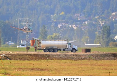 CHILLIWACK, BC/Canada - May 31, 2019: A helicopter hovers beside a water truck during practice training for the upcoming forest fire season near Chilliwack, Canada on May 31, 2019.