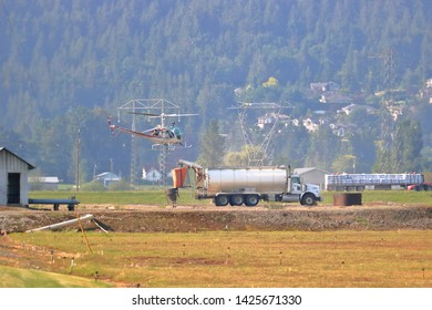 CHILLIWACK, BC/Canada - May 31, 2019: A helicopter pilot in training hovers beside a water tank truck near Chilliwack, BC practicing for the on-coming fire season on May 31, 2019.