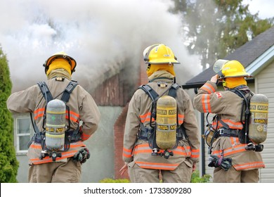 CHILLIWACK,BC/Canada - April 25, 2020: Firefighters in full gear attend a residential fire described as suspicious in Chilliwack,BC,Canada on April 25,2020.