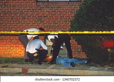 Chillum, Maryland. USA, August 6, 1993Prince Georges County homicide detectives look over the body of 2nd of twin bothers shotgunned to death in front of their family apartment during the crack wars