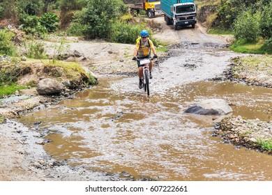 Chimaltenango, Guatemala - December7, 2016: Godinez, Guatemala - December 7, 2017: Cyclist is traveling thru Guatemalan highlands, crossing the river in Chimaltenango distict in Guatemala.