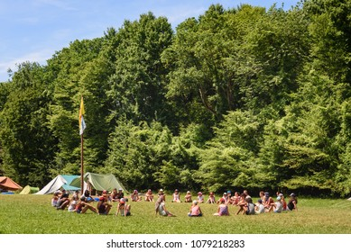 CHIMAY, BELGIUM. JULY 9, 2017. Group of scout teenagers sitting in circle on grass at campsite with youth organisation summer camp in Wallonia, Belgium.