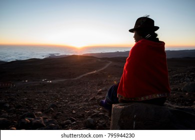 Chimborazo providence at Chimborazo volcano, Ecuador 21/sep/2013 a young indigenous, resting on a rock waiting to the sun to set over the clouds.
