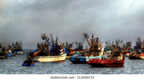 Chimbote, Peru - April 17, 2018: Trawlers and boats moored at Chimbote, Peru with cloud covered mountain in background