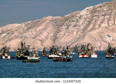 Chimbote, Peru - April 17, 2018: Trawlers and boats moored at Chimbote, Peru with white mountain in background