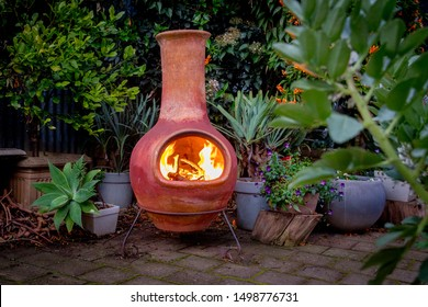 A Chimenea in the backyard.  A backyard fire place surrounded by plants.