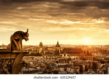 Chimera (gargoyle) of the Cathedral of Notre Dame de Paris overlooking Paris at sunset, France. Panorama of the city in the sunlight, view from Notre Dame.