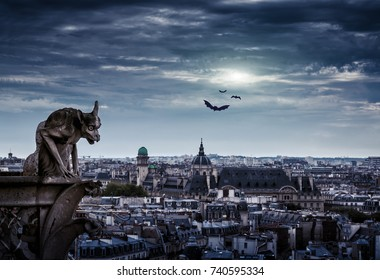 Chimera (gargoyle) of Cathedral of Notre Dame de Paris overlooking city on Halloween, France. Paris skyline at night. Fantasy mystic view of Paris at dusk. Gloomy panorama of old town in moonlight.