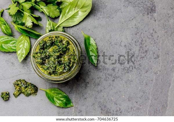 Chimichurri sauce. Argentine green parsley basil sauce chimichurri for barbecue asado in glass jar, gray slate background.