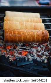 A chimney cake is baked over an open charcoal grill.