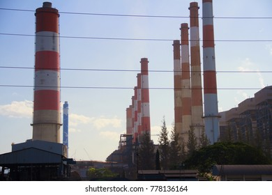 Chimney of electric power plant generate electricity send to power transmission towers line to bring electrical energy to the country, province or other industries.