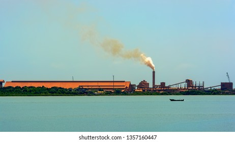 A chimney emits smoke at a bauxite industrial complex on the coast at Guinea, West Africa.