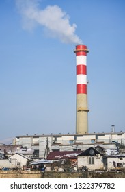 Chimney of a factory exhausting toxic and harmful smoke near a poor suburb