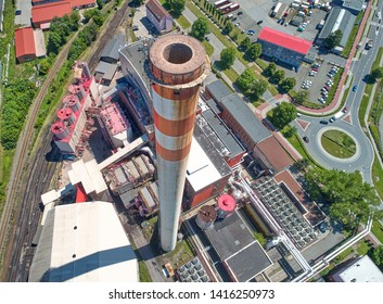 Chimney of a heating plant, hundreds of meters high. Aerial view of top of chimney and city in background. Energy industry, air pollution.