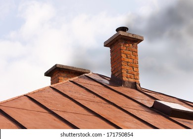 Chimney with neglected maintenance emitting air pollution due to improper burn of solid fuels in wood stove during heating season.