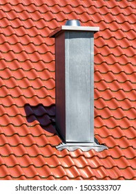 Chimney on clean roof of residential house. Modern air vent system on rooftop of building. Vertical view of metal chimney pipe on background of red tiles. Steel home chimney close-up in summer.
