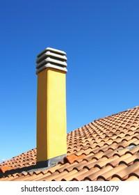 Chimney on roof on blue sky background