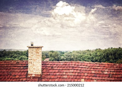 Chimney on a rooftop with clouds on grungy background