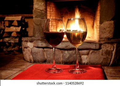 Chimney place wine party concept. Two glasses of red white wine, fireplace background. romantic xmas postcard, cozy interior of a xmas evening