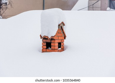 chimney in red bricks with own roof covered with tons of white snow on the roof of the house caused by storm so called the beast from the east