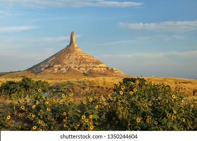 Chimney Rock National Historic Site with sunflowers, western Nebraska, USA. The peak of Chimney Rock is 1289 meters above sea level.