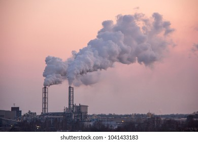 Chimney smoking stack. Air pollution and climate change theme. Poor environment in the city. Environmental disaster. Harmful emissions into the environment. Smoke and smog.