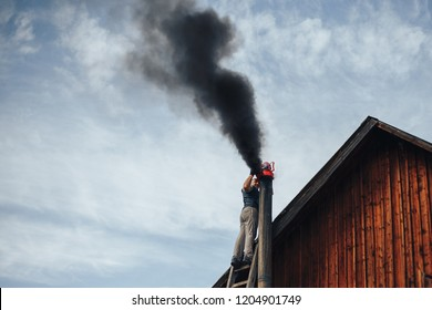 Chimney sweep cleaning a chimney standing balanced on the apex of a house roof lowering equipment down the flue