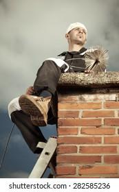 Chimney sweep man in uniform sitting on brick chimney