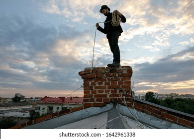 Chimney sweep young man with beard and dirty face on the roof