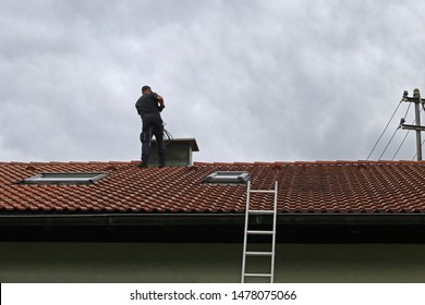 A chimney sweeper on the roof cleans a chimney with a brush.