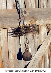 Chimney sweeper tools close up metal wire brush with weight and rope on weathered wooden wall background