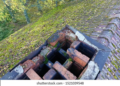Chimney is in very bad condition and needs urgent repair before it collapses. Mortar joints are gone or cracked and bricks are loose. Mossy tile roof on background.