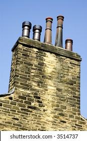 Chimneys on old building against blue sky
