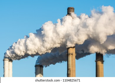 The chimneys of a powerstation with huge smoke stacks and a blue sky as background.