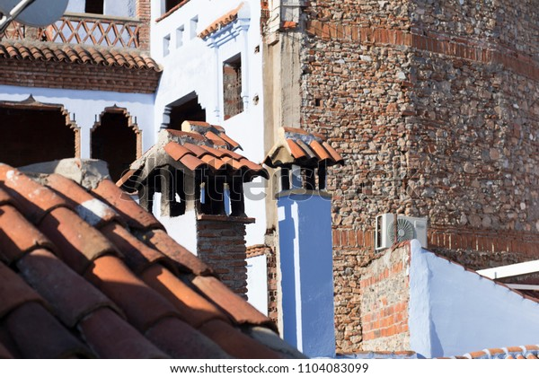 chimneys, roofs, blue and red colors in the Moroccan village of Chefchaouen
