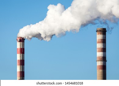chimneys and smoke over combined heat and power station during sunny day