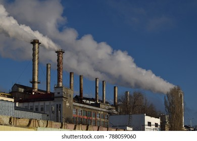 Chimney-stalk let out a thick smoke against the blue sky. Pollution of the atmosphere by industrial enterprises.