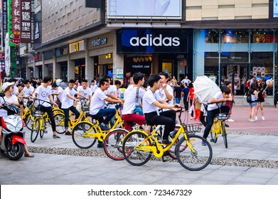 China Bike-Sharing Scene. Group of Men Ride Yellow Bikes by OfO Company, at the Popular Commercial Street Called Huangxinglu, Changsha City, Hunan Province, China, July, 2017.