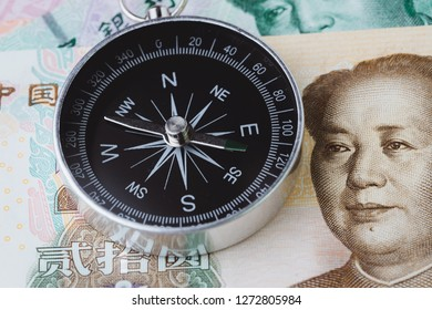 China economy direction slow down impacted by trade war, world emerging market slow growth country concept, closed up of compass on Chinese Yuan banknotes on table.