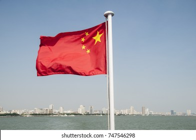 the china flag blowing on the windy day at the seashore with the cityscape behind it