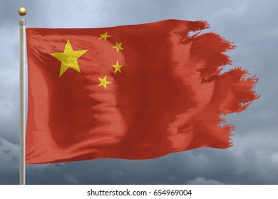 China Flag with torn edges in front of a stormy sky