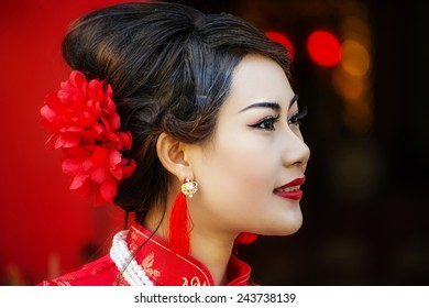China Girl ,Chinese woman red dress traditional cheongsam ,close up portrait with red wood door